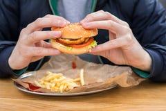 Ciérrese encima de la vista de las manos del ` s del hombre con la hamburguesa americana Fotos de archivo libres de regalías