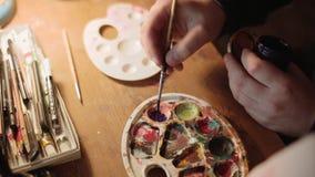 Ciérrese encima de la vista de las manos masculinas de los artist's que trabajan en la pintura El cepillo de las aplicaciones d almacen de video