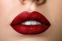 Ciérrese encima de la vista de los labios hermosos de la mujer con el lápiz labial mate rojo Fotos de archivo libres de regalías