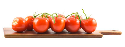 Ciérrese encima de la vista de los pequeños tomates de cereza rojos en un tablero de madera y un fondo blanco Imágenes de archivo libres de regalías