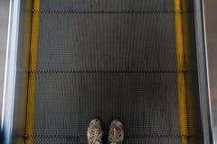 Ciérrese encima de la vista de pies en la escalera móvil Foto de archivo