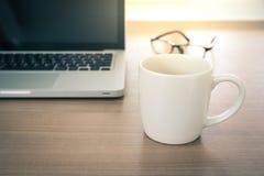Ciérrese encima de la vista de un interior del escritorio del trabajo con un ordenador portátil, A Foto de archivo