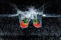 ciérrese encima de la vista del movimiento de las fresas maduras que caen en el agua imágenes de archivo libres de regalías