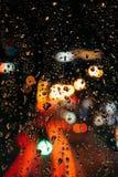 Ciérrese encima de la vista de gotas de agua en luces de la ciudad de la ventana y del bokeh foto de archivo libre de regalías