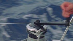 Ciérrese encima de la vista de la mano del ` s del hombre que tuerce la cuerda en el torno del yate de la navegación almacen de video