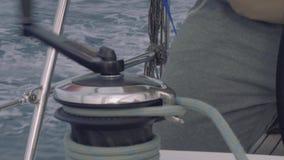 Ciérrese encima de la vista de la mano del ` s del hombre que tuerce la cuerda en el torno del yate de la navegación metrajes