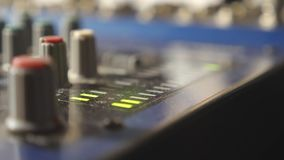 Ciérrese encima de la vista de la mezcladora de audio del mezclador con los botones y los indicadores luminosos verdes que destel almacen de metraje de vídeo