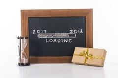 ciérrese encima de la vista de la pizarra con 2017 a 2018 letras cargadas con reloj de arena y el regalo cerca cerca Fotografía de archivo libre de regalías