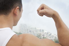 Ciérrese encima de la vista posterior del hombre joven que dobla su bíceps, al aire libre en Pekín, inclinación de la cámara Imágenes de archivo libres de regalías