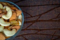 Ciérrese encima de la vista superior de las pasas nuts de las almendras del anacardo en un cuenco en la tabla de madera Fotos de archivo