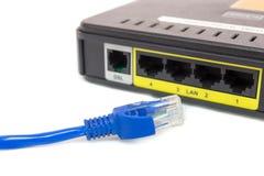 Ciérrese encima de LAN UTP RJ45 Cat5e delante del router de ADSL Fotografía de archivo