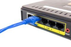 Ciérrese encima de LAN UTP RJ45 Cat5e delante del router de ADSL Fotos de archivo libres de regalías