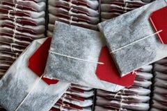 Ciérrese encima de las bolsitas de té con las etiquetas rojas en caja Imagen de archivo libre de regalías