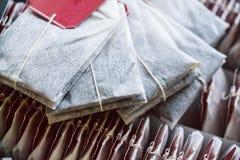 Ciérrese encima de las bolsitas de té con las etiquetas rojas en caja Fotografía de archivo libre de regalías
