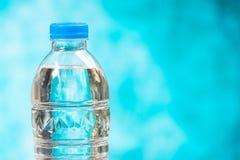 Ciérrese encima de las botellas de agua plásticas con los casquillos en fondo azul Foto de archivo libre de regalías