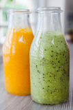 Ciérrese encima de las botellas de smoothies de la fruta Kiwi Naranja Imagen de archivo libre de regalías