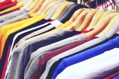 Ciérrese encima de las camisetas coloridas están colgando en el estante imagen de archivo