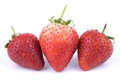 Ciérrese encima de las frutas frescas perfectamente retocadas de las fresas en el fondo blanco Fotografía de archivo libre de regalías