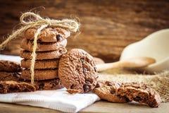 Ciérrese encima de las galletas de microprocesador de chocolate apiladas en servilleta con b de madera Fotografía de archivo libre de regalías
