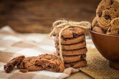 Ciérrese encima de las galletas de microprocesador de chocolate apiladas en servilleta con b de madera Foto de archivo