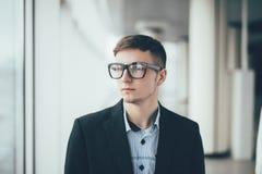 Ciérrese encima de las lentes que llevan sonrientes del hombre de negocios joven, mirando lejos contra pasillo de la oficina Fotos de archivo
