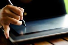 Ciérrese encima de las manos con la escritura de la pluma en la tableta gráfica moderna Imagenes de archivo