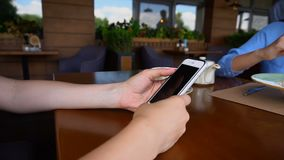 Ciérrese encima de las manos con los clavos largos que hojean por smartphone en el café durante almuerzo almacen de metraje de vídeo