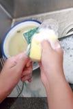 Ciérrese encima de las manos de la cuchara que se lava de la mujer con la esponja y la espuma Imagen de archivo