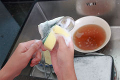 Ciérrese encima de las manos de la cuchara que se lava de la mujer con la esponja y la espuma Imagen de archivo libre de regalías