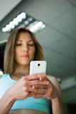Ciérrese encima de las manos de la mujer con smartphone en el gimnasio Fotografía de archivo libre de regalías