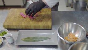 Ciérrese encima de las manos del cocinero en el uniforme blanco del restaurante que corta pequeños pescados de color salmón almacen de metraje de vídeo