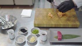Ciérrese encima de las manos del cocinero en el uniforme blanco del restaurante que corta pequeños pescados de color salmón Artíc almacen de video