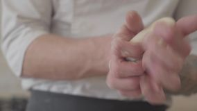 Ciérrese encima de las manos del fabricante joven de la pizza en las bolas rodantes de la pasta del uniforme del cocinero para la almacen de metraje de vídeo