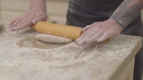 Ciérrese encima de las manos del fabricante joven de la pizza en el delantal que prepara la pasta usando el rodillo de la pasta e almacen de video