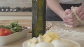 Ciérrese encima de las manos del fabricante joven de la pizza en el uniforme del cocinero kneeding hábilmente la pasta para la pi almacen de video