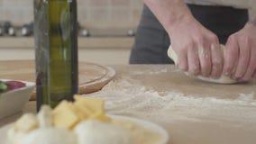 Ciérrese encima de las manos del fabricante joven de la pizza en el uniforme del cocinero kneeding hábilmente la pasta para la pi almacen de metraje de vídeo