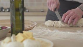 Ciérrese encima de las manos del fabricante joven de la pizza en el uniforme del cocinero que corta la pasta para la pizza con el metrajes