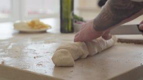 Ciérrese encima de las manos del fabricante joven de la pizza en el uniforme del cocinero que corta la pasta para la pizza con el almacen de metraje de vídeo