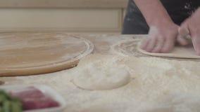 Ciérrese encima de las manos del fabricante joven de la pizza en el uniforme del cocinero que forma una pasta de amasamiento de l almacen de metraje de vídeo