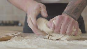 Ciérrese encima de las manos del fabricante joven de la pizza en la pasta de amasamiento del uniforme del cocinero para la pizza  almacen de video