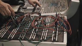 Ciérrese encima de las manos del hombre que sacan y enchufe los alambres en la consola de mezcla de la música metrajes