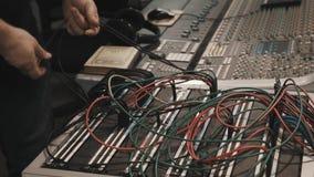 Ciérrese encima de las manos del hombre que tiran de la porción de alambres en la consola de mezcla de la música metrajes