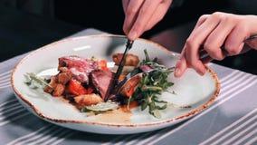 Ciérrese encima de las manos del ` s de la mujer con el cuchillo y la carne del corte de la bifurcación en ensalada en plato en l almacen de video