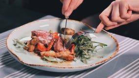 Ciérrese encima de las manos del ` s de la mujer con el cuchillo y la carne del corte de la bifurcación en plato en la tabla en u almacen de metraje de vídeo