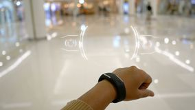 Ciérrese encima de las manos del tiro de la mujer que usa el reloj elegante con la interfaz de usuario de HUD para el concep futu almacen de metraje de vídeo
