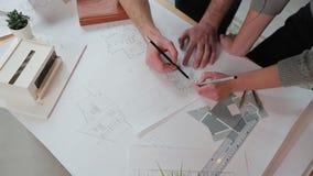 Ciérrese encima de las manos de dos trabajadores que discuten construyendo dibujos en oficina Tiroteo del primer de las imágenes  almacen de video