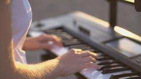 Ciérrese encima de las manos femeninas que juegan el piano con el finger en acorde y la puesta del sol ligera en izquierda, y cop almacen de video