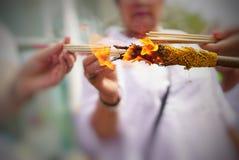 Ciérrese encima de las manos de la gente que sostienen los palillos del incienso por el fuego Imagenes de archivo