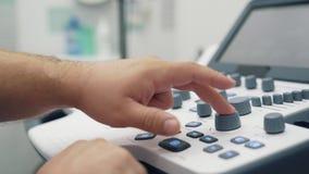 Ciérrese encima de las manos de los botones y de los trabajos de las prensas del doctor sobre el dispositivo del ultrasonido almacen de metraje de vídeo