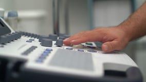 Ciérrese encima de las manos de los botones y de los trabajos de las prensas del doctor sobre el dispositivo del ultrasonido metrajes